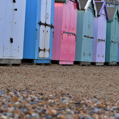 Series of brightly coloured beach huts o