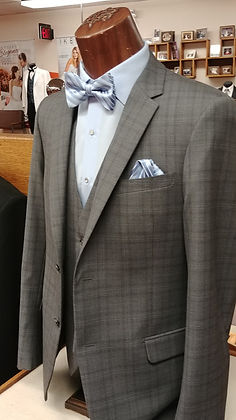 A fashionable grey plaid suit with light blue shirt and bow tie