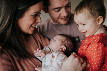 Family adoring baby and toddler
