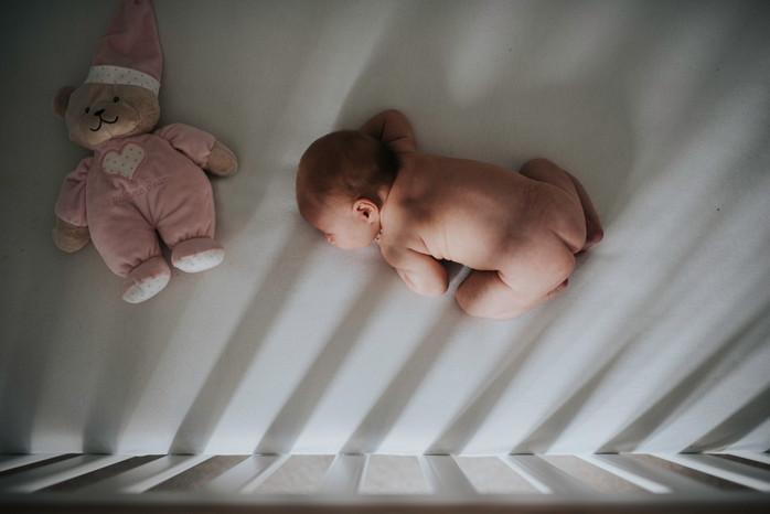 Newborn baby asleep in cot