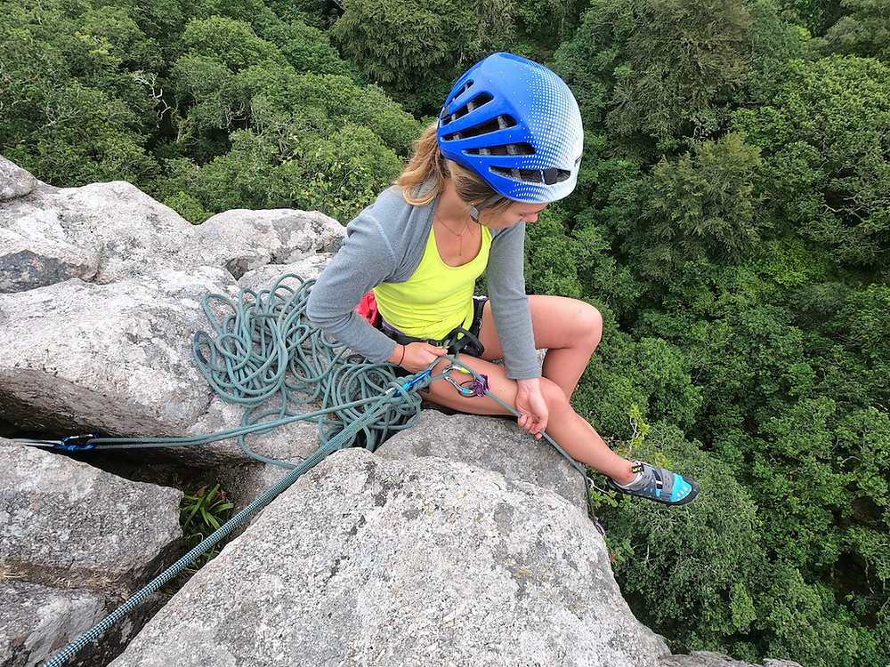 Climber attached to anchors using the climbers rope at the top of a climb