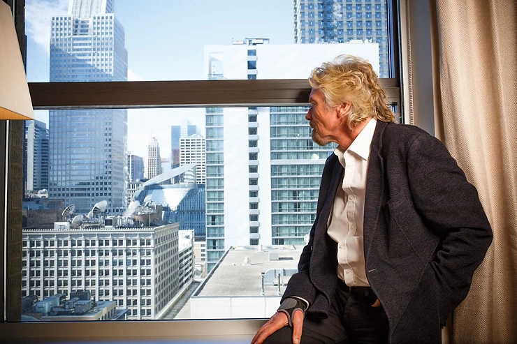 Richard Branson looking out of a window of Virgin Hotels