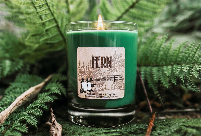 Fern scented jar candle nestled in front of green ferns in forest