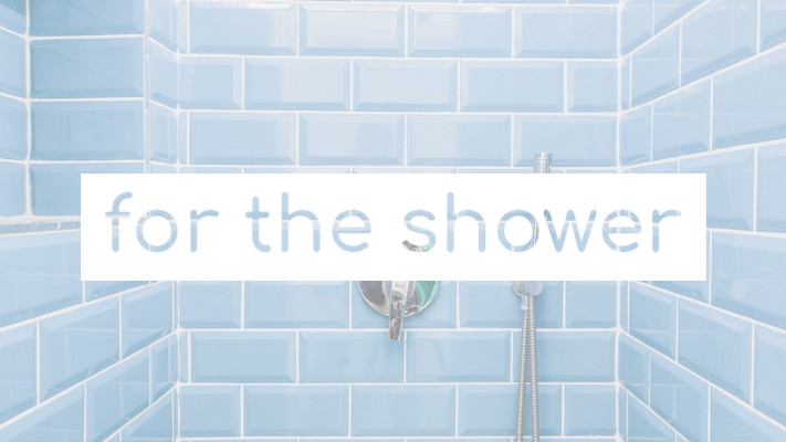 Blue shower tiles with shower head and white text box
