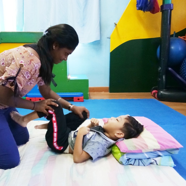 Psysiotherapist working on a cp child : doing his stretches lower body
