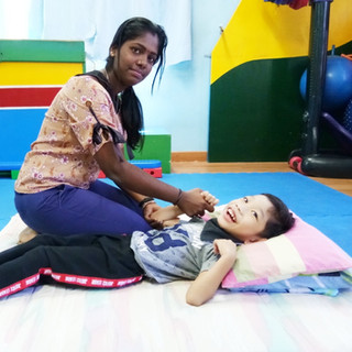 Psysiotherapist working on a cp child : doing his stretches