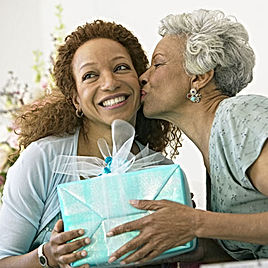 A Mom giving a gift to her Daughter with a Kiss