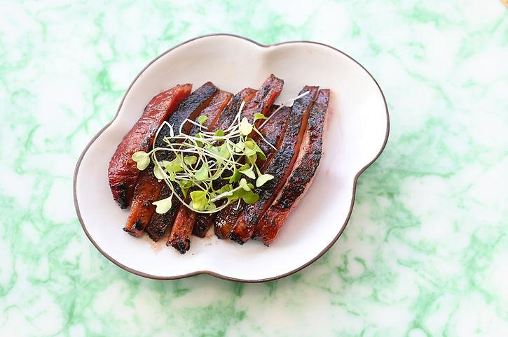 Our cha siu pork jowl on a white clover plate