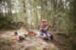 a girl holding a doll sitting in a forrest