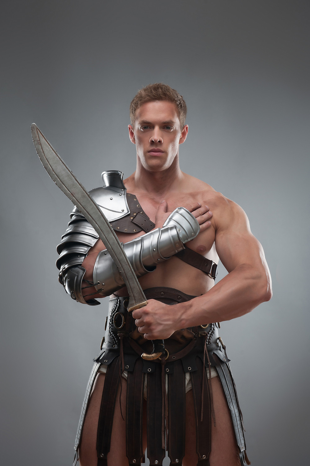 Gladiator in armour posing with sword over grey background.jpg