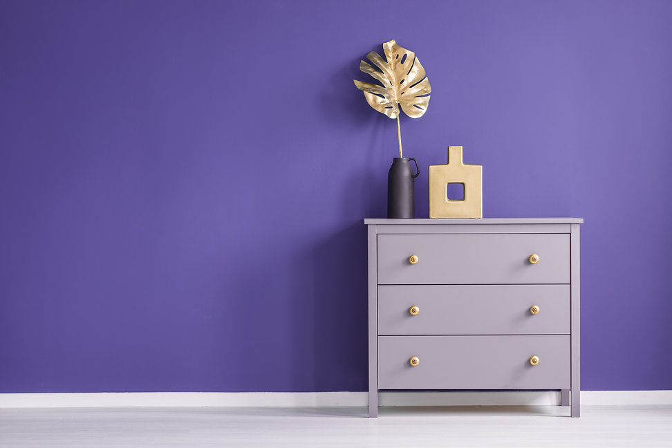 Chest of drawers with golden knobs, vase