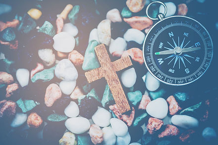 Close up of wooden cross and compass on
