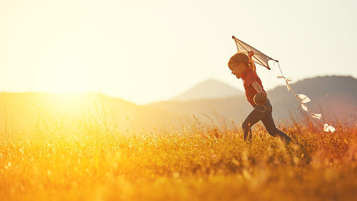 happy child girl with a kite running on