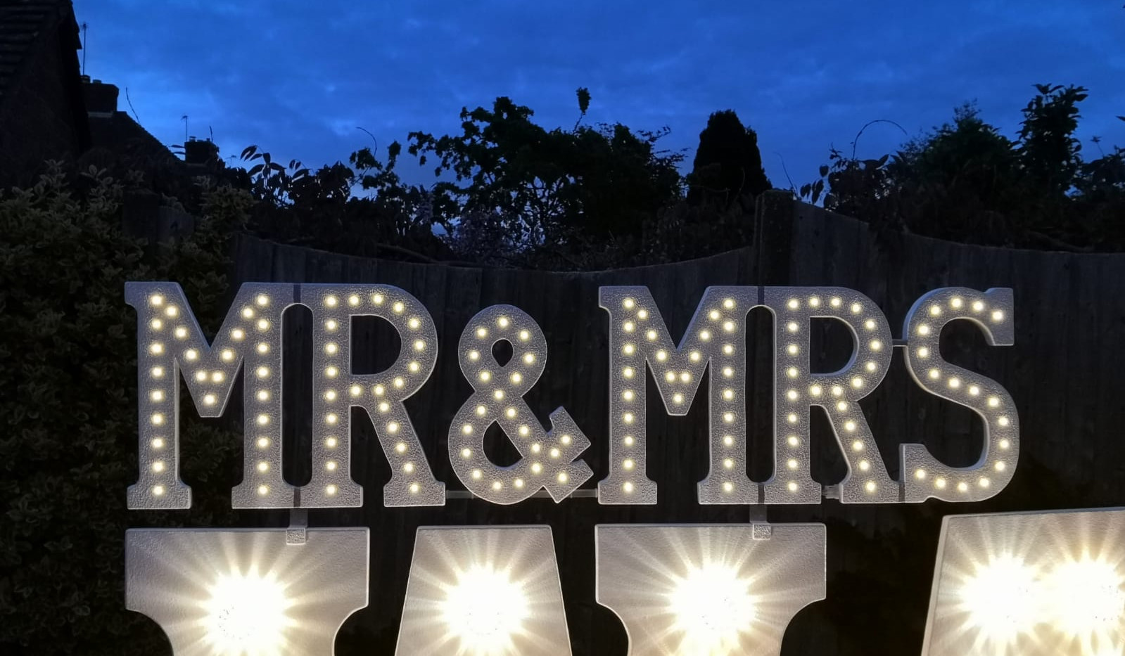 Mr & Mrs small letter lights on top of surname letter lights to hire