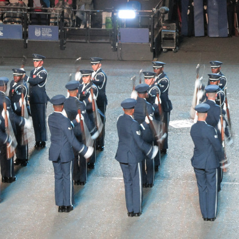 The USAF Hnour Guard Drill Team tossing their rifles in the air with sharp bayonets attched.