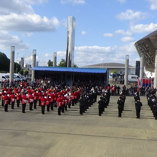 The Massed Band and choir perform during the finale with the arching Wales Millenium Center in the backround