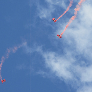 3 members of the Red Devils Parchute Display flying over the skies of Cardiff Bay