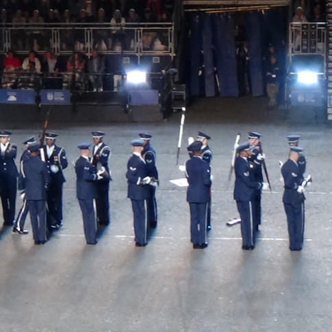 Captain Riley Platt of the USAF Honour Guard Drill Team walking through  his team throwing their rifles, with beyonets in front of him.