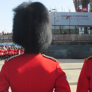 Members of the 1st Battalion Welsh Guards and Queen's Dragoon Guards (Welsh Cavalry) stand at ease and watch as the final band leaves the arena.