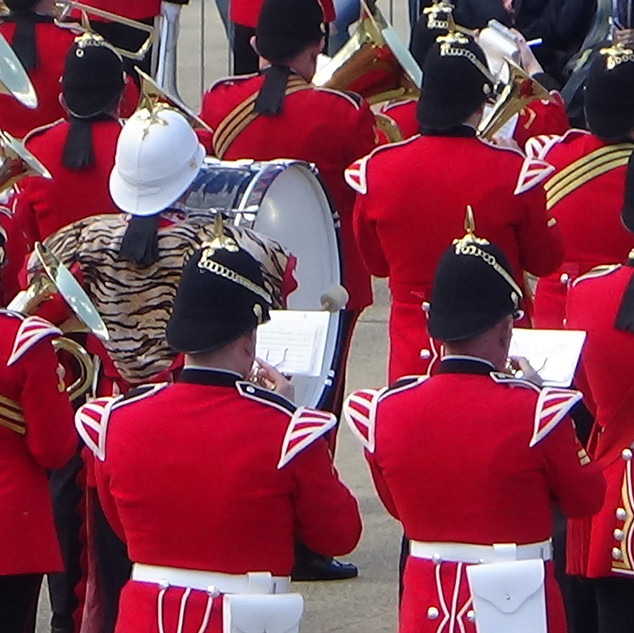 The Regimental Coprs of Drums of the Royal Welsh's Bass Drummer's White Pith Helmet in the middle of the combined brass band.