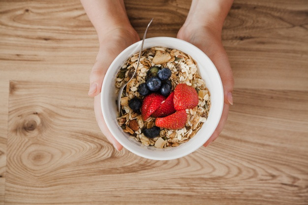 Top view of person holding muesli bowl Free Photo