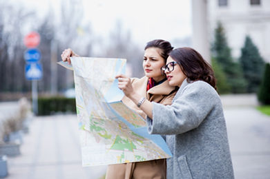 Two girls are lost and guided by the map in the city. Both coat and brunettes. In autumn or in sprin