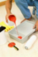 schilder doet rode verf in schildersbak