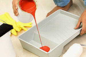 Person wearing jeans pours bright red pain into a white painting tray in preparation to pain a room