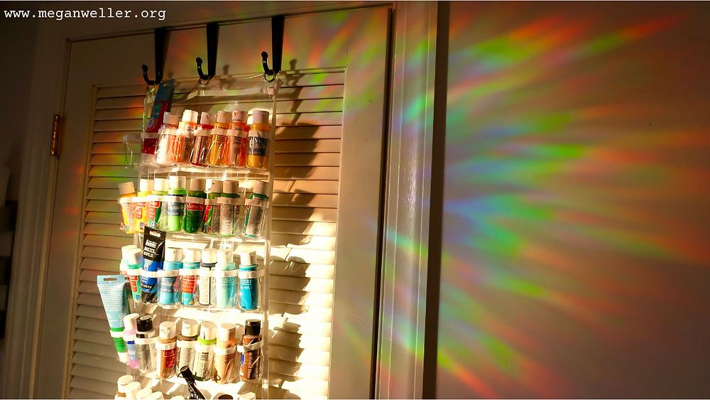 Rainbow window film, rainbow window decal shining on the wall. The wall has hanging acrylic paint wall storage.