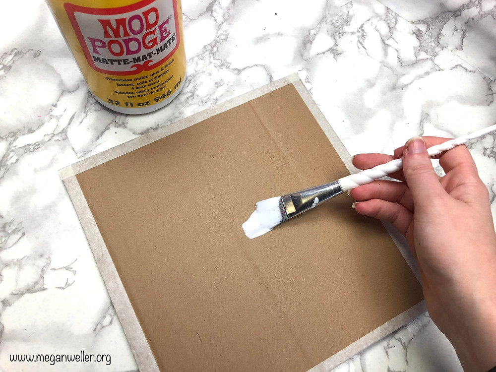 Painting Mod Podge on top of cardboard.