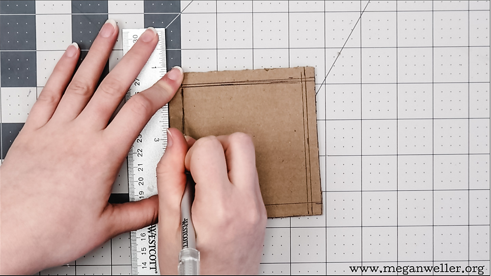 Using an X-Acto knife to cut the center out of a cardboard square.