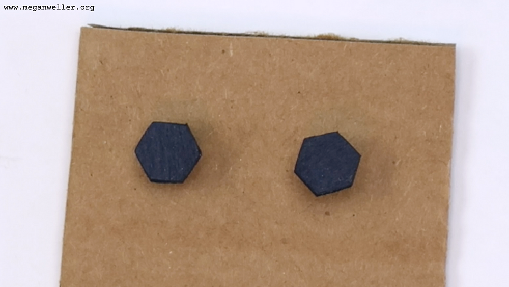 Poke the earrings into some cardboard to make them easier to decorate.