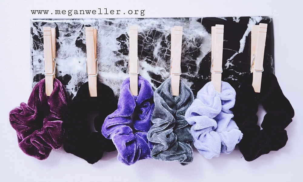 Finished DIY Clothespin Wall organizer holding purple, gray, and black scrunchies. How to organize scrunchies.