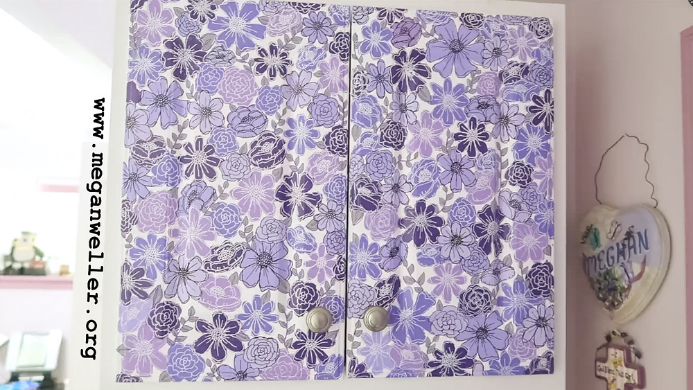 White Bathroom cabinet customized by painting purple flowers on the doors. The flowers were inspired by ktscanvases on tiktok.