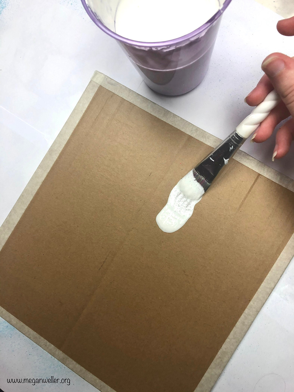Homemade Gesso being painted on cardboard to make a canvas panel.