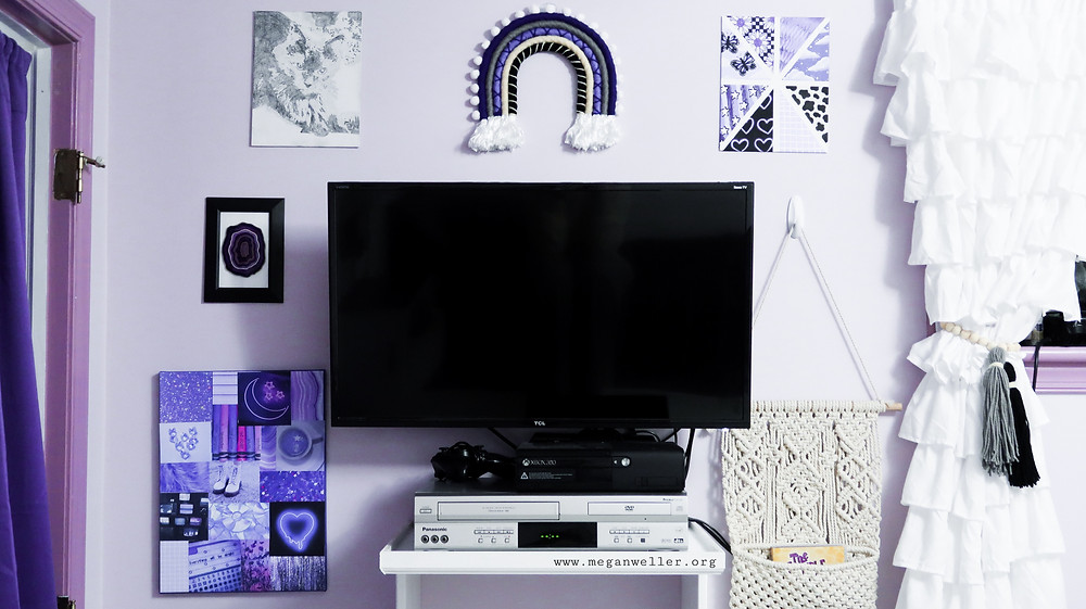 "Gallery wall around a TV in a purple bedroom. The gallery wall features a diy photo canvas, a shrink dink geode, a drawing of as cat, a rainbow wall hanging, an ""aesthetic"" painting, and a macrame wall pocket."