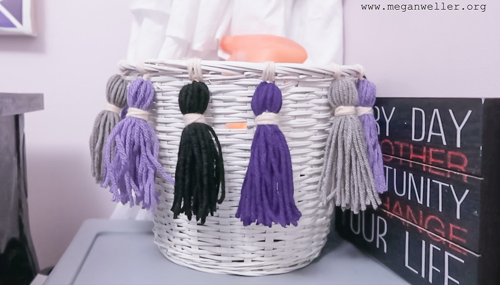 White basket decorated with small purple, gray, black, and white yarn tassels.