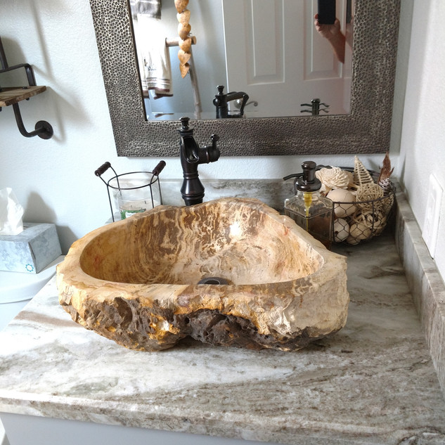 Construction remodeling project with a farmhouse rustic theme including rock sink on counter top of this this unique guest bath remodel