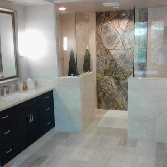 Construction remodeling project with a stunning marble wall and marble bench in shower included in this upscale master bath remodeling project