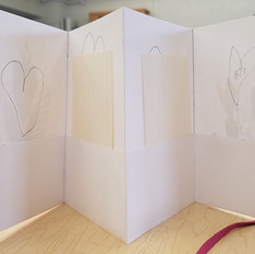Students learned  how to create their own 'End Papers'. This student cut out heart shapes from collage paper. They were used as a design element to hide the exposed end of the ribbon. Ribbons are used to tie their books closed.  This book also shows a pocket fold I taught them how to make when they were creating the folds of their accordion books.   The pocket fold holds cards they would later write on for National Poetry Month, which is in April.