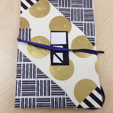 A final accordion book  showing it with a ribbon closure around the collaged  cover.