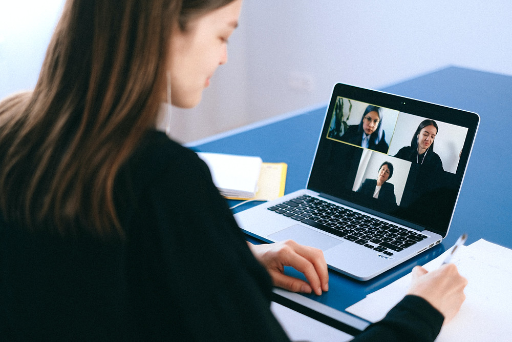 A young woman taking notes while on a Zoom call with three other women using her MacBook