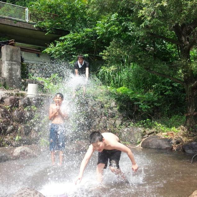 山水で遊ぶ子供達
