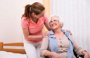 Pflegefachkraft bei der täglichen Betreuung einer Rollstuhlfahrerin