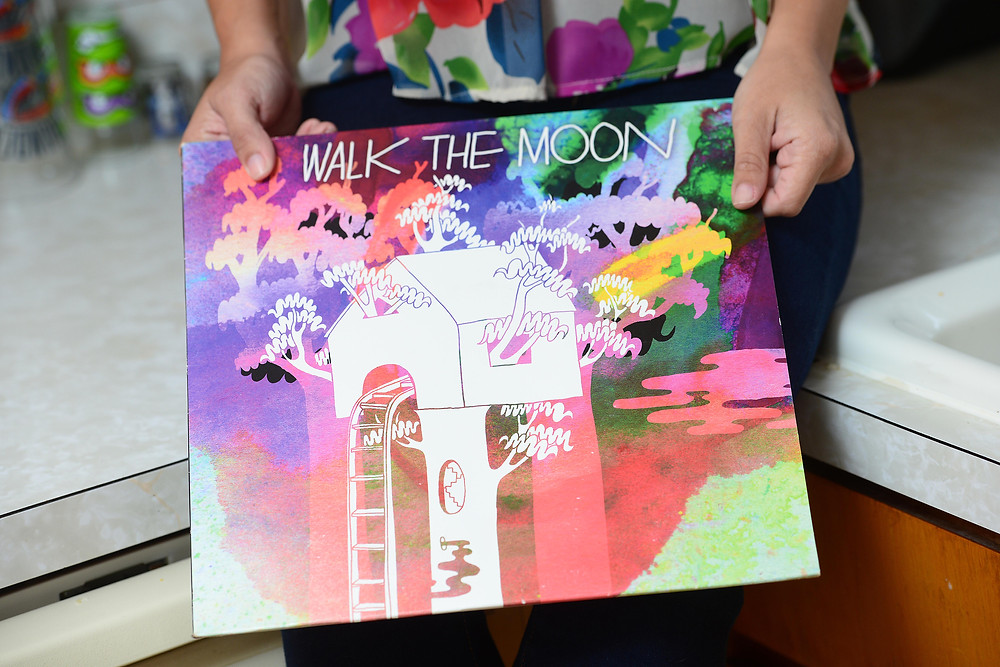 A music blogger holds the self-titled vinyl record by Walk the Moon.