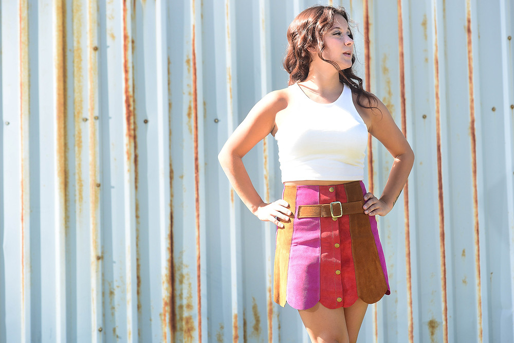 A style blogger wears a brightly-colored vintage suede skirt.