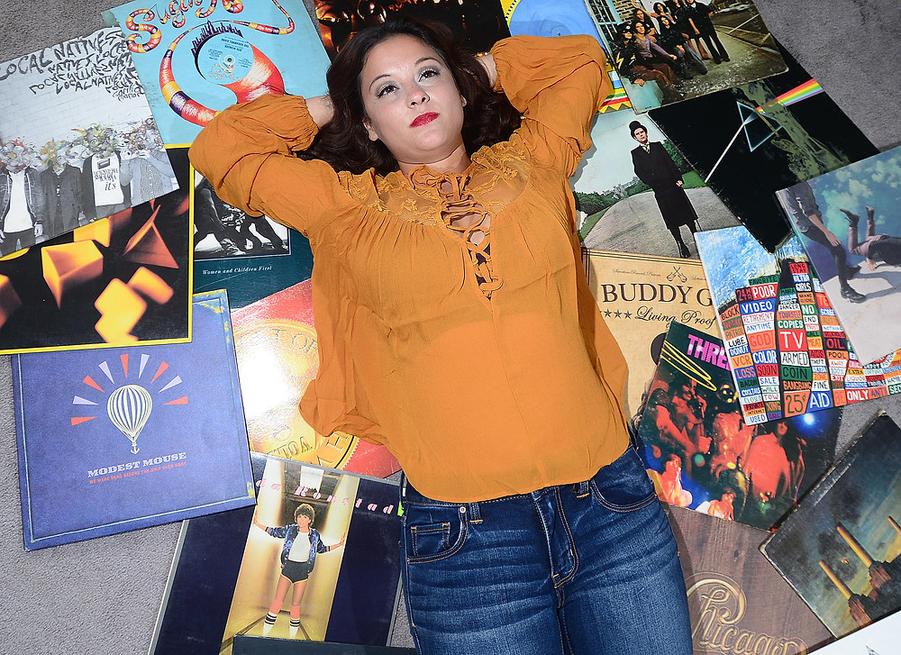 A music blogger and vinyl record collector poses with a section from her vinyl record collection.