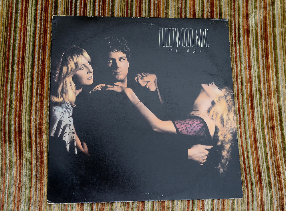 "The vinyl record ""Mirage"" by Fleetwood Mac sits on a striped vintage couch."