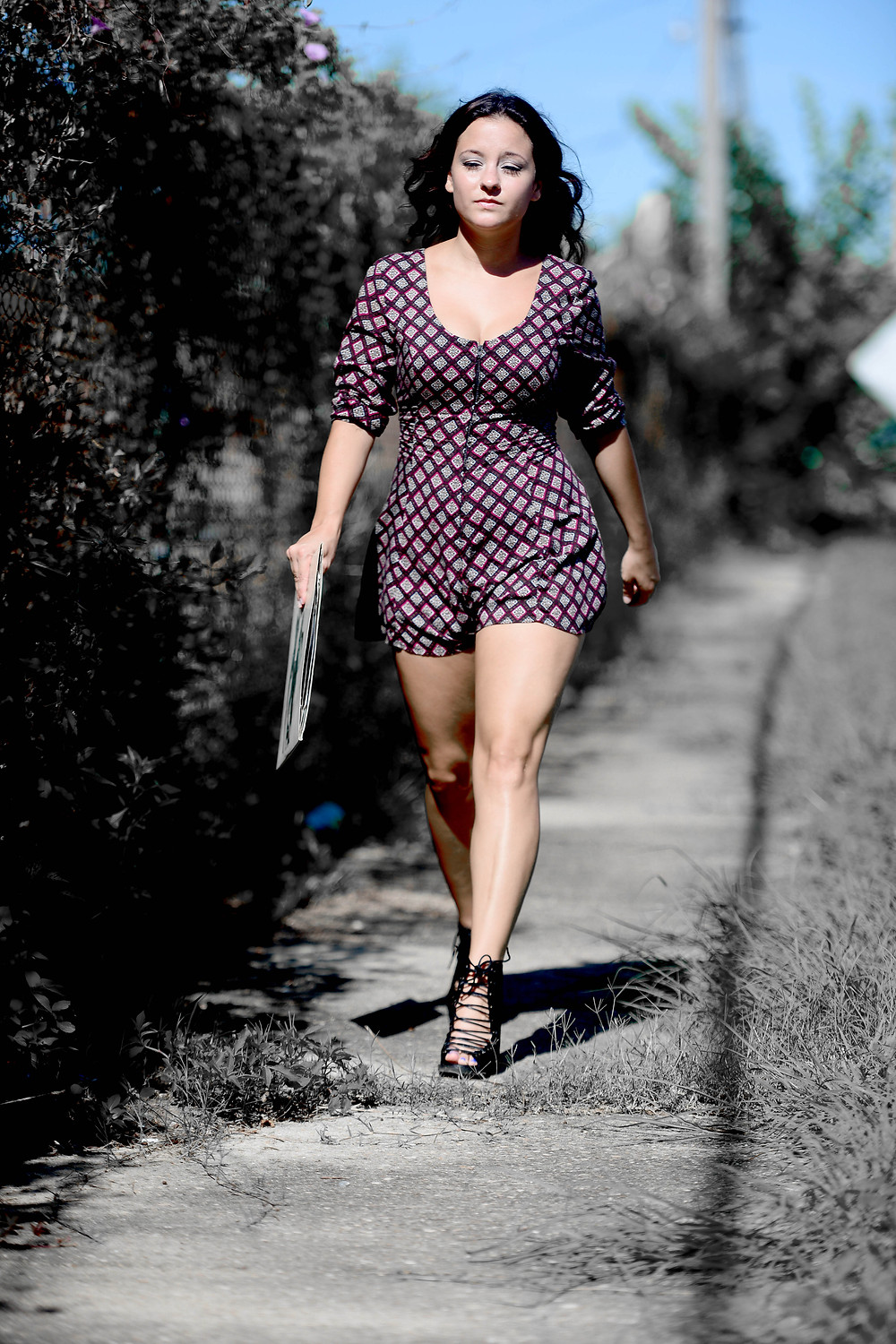 A fashion blogger walks down the sidewalk in an Urban Outfitters romper.
