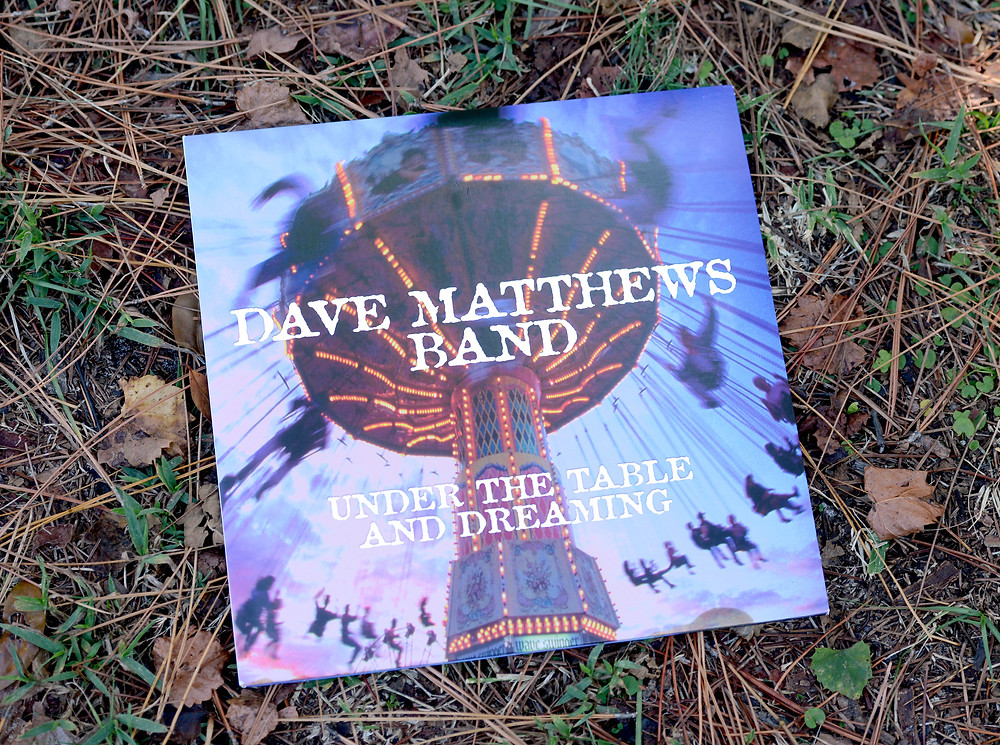 "Dave Matthews Band's vinyl record ""Under the Table and Dreaming"" sits in the grass."